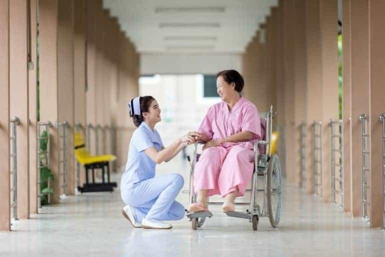 Nurse on one knee speak to patient in wheelchair
