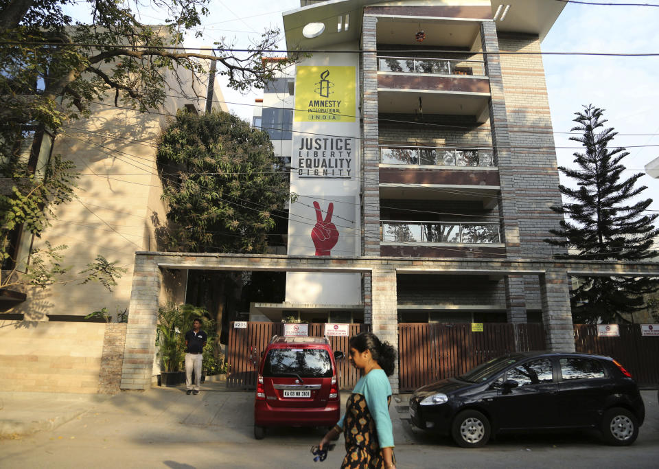 FILE - In this Tuesday, Feb. 5, 2019, file photo, a woman walks past the Amnesty International India headquarters in Bangalore, India. The U.N. human rights chief Michelle Bachelet on Tuesday, Oct. 20, 2020, urged India's government to do more to protect the rights of human rights defenders, who have come under mounting pressure in recent months in the world's largest democracy. Last month, advocacy group Amnesty International halted its operation in India, citing reprisals by the government and the freezing of its bank accounts by Indian authorities. (AP Photo/Aijaz Rahi, File)
