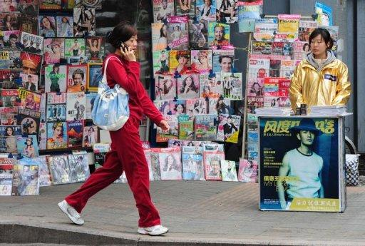 A woman works at a magazine stall in in Beijing on April 10, 2012. Analysts still widely expect China to record a trade surplus for the full year, helped by lower commodity prices and a recovery in exports, but much smaller than 2011