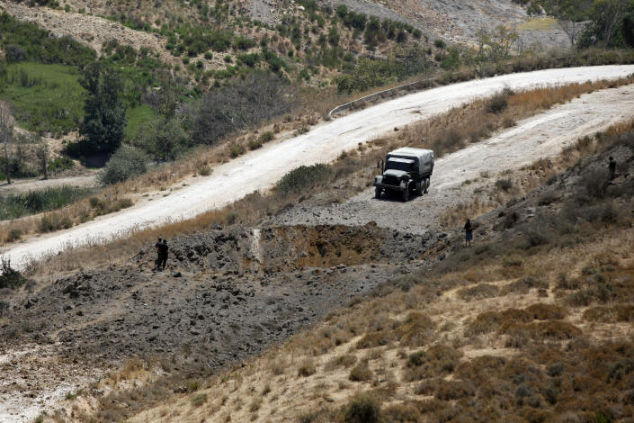 FILE - In this Aug 5, 2021 file photo, Lebanese troops stand next to a crater caused by an Israeli airstrike in Dimashqiya farmlands, southern Lebanon. As Lebanon sinks deeper into poverty and collapse, many Lebanese are more openly criticizing the Iran-backed Hezbollah, blaming it for its role in the devastating, multiple crises plaguing the country. This includes a dramatic currency crash and severe shortages in medicines and fuel that has paralyzed the country. (AP Photo/Mohammed Zaatari, File)