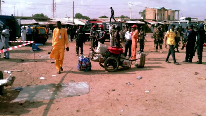 People and security personnel stand at the scene of a blast in the northern Nigerian city of Kano, on July 24, 2014 (AFP Photo/Aminu Abubakar)