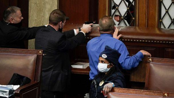 PHOTO: Police with guns drawn watch as protesters try to break into the House Chamber at the U.S. Capitol, Jan. 6, 2021, in Washington. (J. Scott Applewhite/AP)