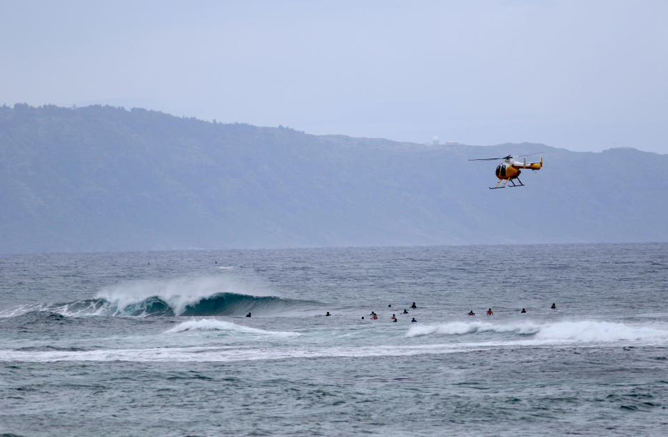 """In this March 31, 2020 file photo a fire and rescue helicopter flies over a group of surfers on Oahu's North Shore near Haleiwa, Hawaii. Former Hawaii television reporter Angela Keen knows how to track people down. During the coronavirus pandemic, she's putting her people-finding skills to use as one of the original members of a Facebook group that has grown to more than 2,000 people called """"Hawaii Quarantine Kapu Breakers."""" Kapu is a Hawaiian word that means laws or rules. The group is focused on finding people who violate Hawaii's 14-day quarantine on travelers arriving to the state. (AP Photo/Caleb Jones,File)"""