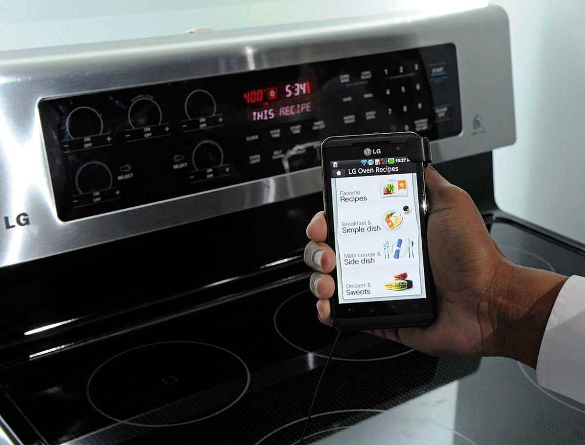 LAS VEGAS, NV - JANUARY 11: A smartphone sending instructions to an oven using LG's newest Smart ThinQ technology is demonstrated at the LG Electronics booth at the 2012 International Consumer Electronics Show at the Las Vegas Convention Center January 11, 2012 in Las Vegas, Nevada. LG's line of smart home appliances coming out in 2012, have improved connectivity between them and other devices like phones and TVs, allowing for easier control and monitoring of the devices. CES, the world's largest annual consumer technology trade show, runs through January 13 and features more than 3,100 exhibitors showing off their latest products and services to about 140,000 attendees. (Photo by Ethan Miller/Getty Images)