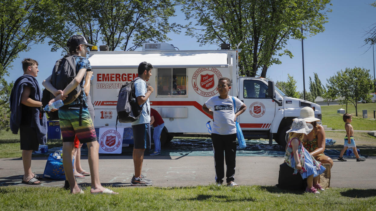 A Salvation Army EMS vehicle is setup as a cooling station as people lineup to get into a splash park while trying to beat the heat in Calgary, Alberta, Wednesday, June 30, 2021. Environment Canada warns the torrid heat wave that has settled over much of Western Canada won't lift for days. (Jeff McIntosh/The Canadian Press via AP)
