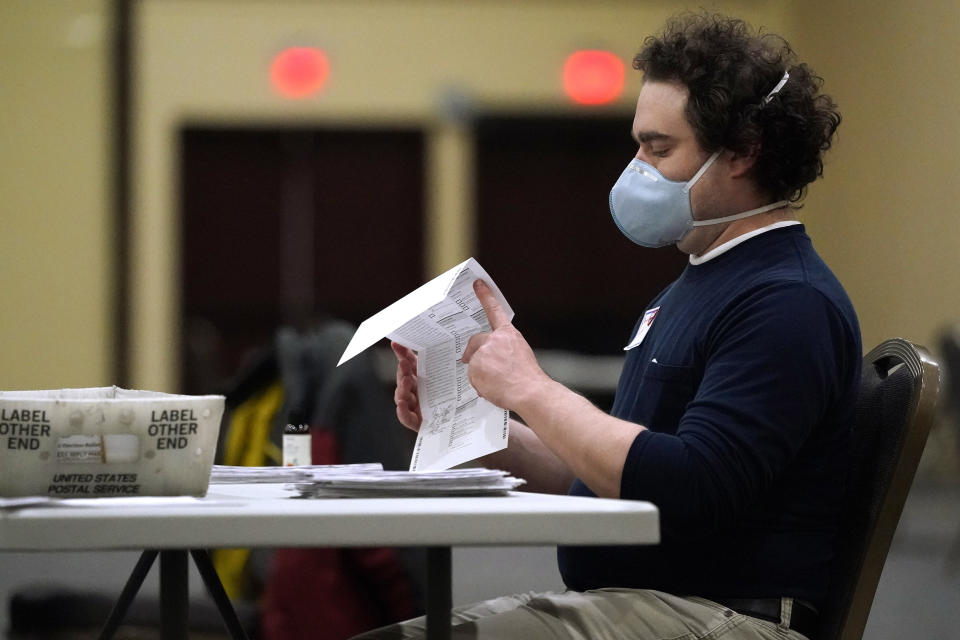 A worker opens a mail-in ballots to prepare them for counting, Wednesday, Nov. 4, 2020, at the convention center in Lancaster, Pa., following Tuesday's election. (AP Photo/Julio Cortez)