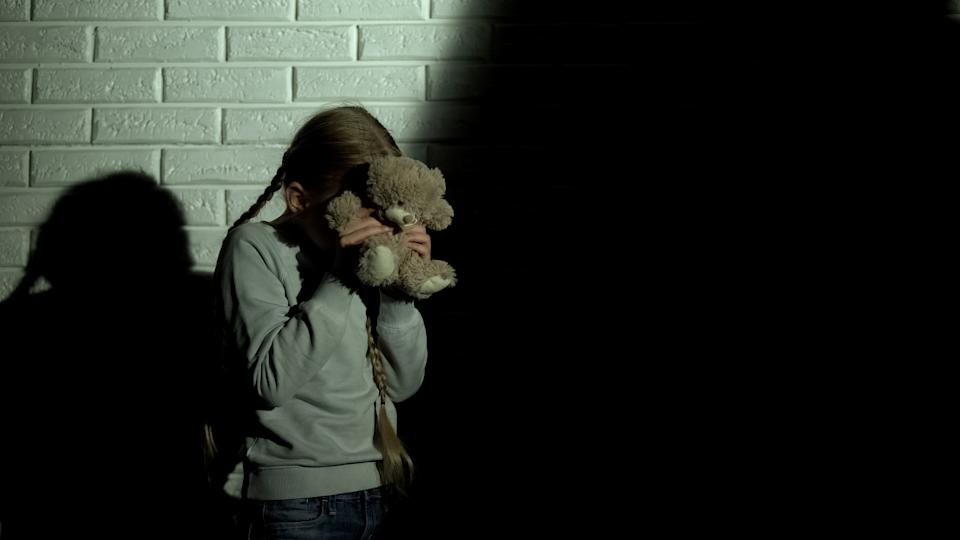 Girl with bear covering her eyes.