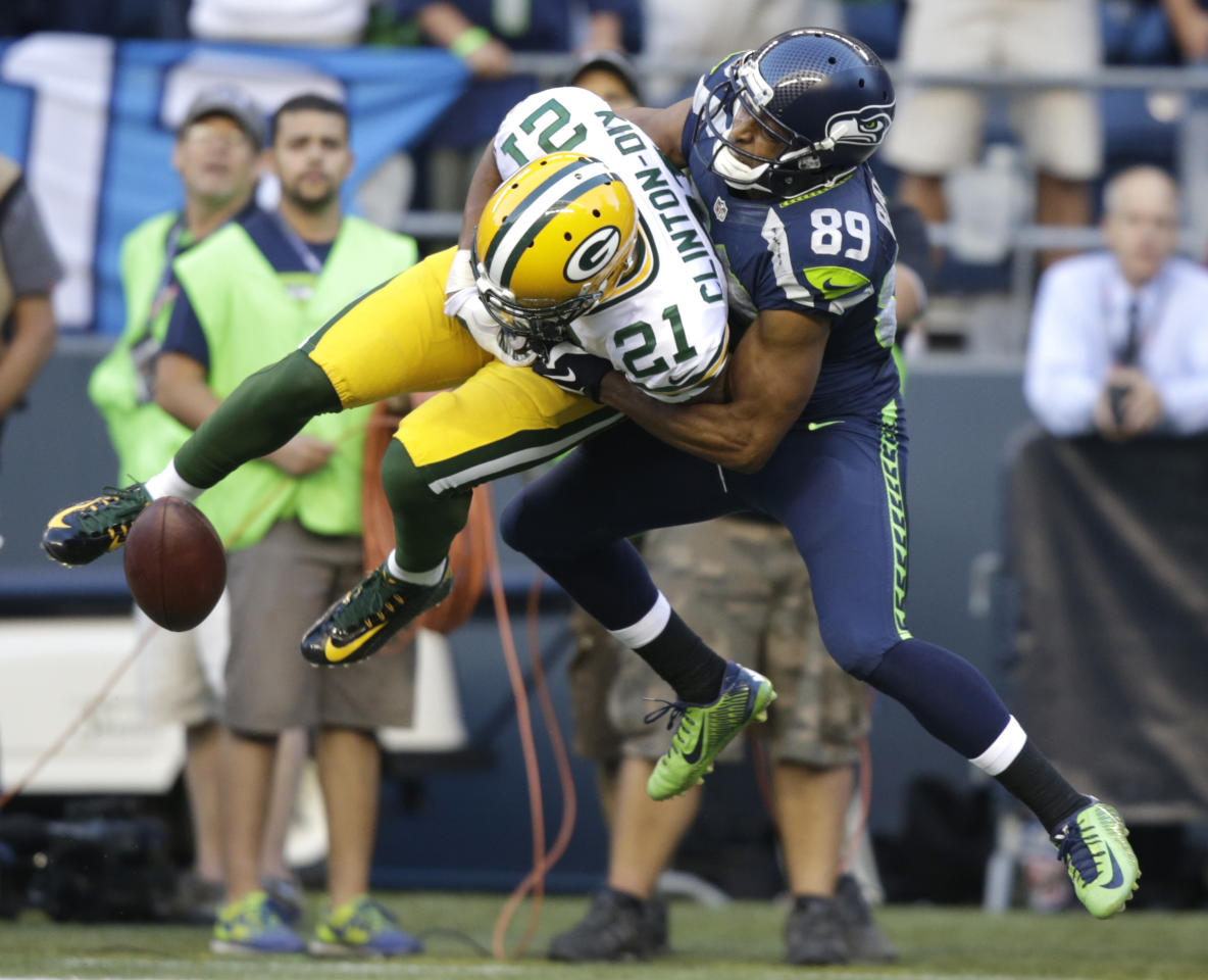 Seattle Seahawks' Doug Baldwin, right, breaks up an interception attempt by Green Bay Packers free safety Ha Ha Clinton-Dix (21) in the first half of an NFL football game, Thursday, Sept. 4, 2014, in Seattle. (AP Photo/Stephen Brashear)