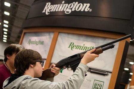 A boy aims a Remington firearm at the annual National Rifle Association (NRA) meeting in Dallas, Texas, U.S., May 4, 2018. REUTERS/Adrees Latif