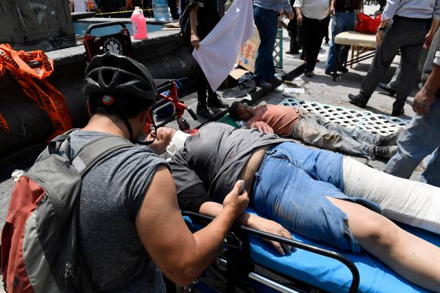 <p>A woman is assisted after being injured during a quake in Mexico City on September 19, 2017.<br> A powerful earthquake shook Mexico City on Tuesday, causing panic among the megalopolis' 20 million inhabitants on the 32nd anniversary of a devastating 1985 quake. The US Geological Survey put the quake's magnitude at 7.1 while Mexico's Seismological Institute said it measured 6.8 on its scale. The institute said the quake's epicenter was seven kilometers west of Chiautla de Tapia, in the neighboring state of Puebla.<br> (Photo: Omar Torres/AFP/Getty Images) </p>