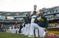 Bruce Maxwell #13 (R) of the Oakland Athletics kneels during the national anthem prior to the game against the Texas Rangers at the Oakland Alameda Coliseum on September 23, 2017 in Oakland, California. The Athletics defeated the Rangers 1-0. (Photo by Michael Zagaris/Oakland Athletics/Getty Images)