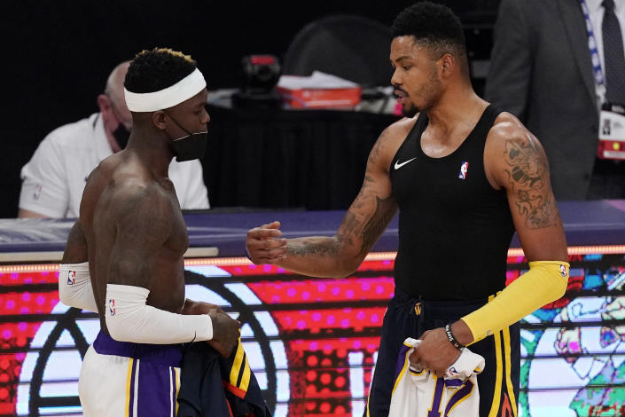 Los Angeles Lakers guard Dennis Schroder, left, and Golden State Warriors forward Kent Bazemore trade jerseys after an NBA basketball game Sunday, Feb. 28, 2021, in Los Angeles. The Lakers won 117-91. (AP Photo/Mark J. Terrill)
