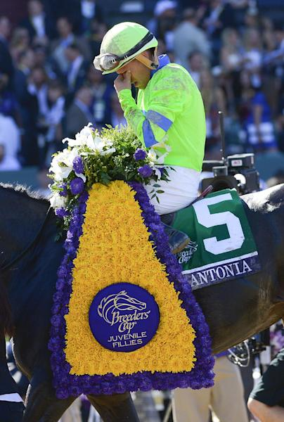 Jockey Javier Castellano, wipes his face after Ria Antonia won the Breeders' Cup Juvenile Fillies horse race, after getting bumped by jockey Gary Stevens riding She's a Tiger at Santa Anita Park Saturday, Nov. 2, 2013, in Arcadia, Calif. (AP Photo/Mark J. Terrill)