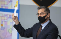 U.S. Department of Health and Human Services (HHS) Secretary Xavier Becerra holds up a flier promoting the Vax Nevada Days lottery after briefing from officials at the Clark County Fire Department Training Facility in Las Vegas Thursday, July 22, 2021. The vaccine lottery awards cash and prizes to Nevada residents who have received the COVID-19 vaccine. (Steve Marcus /Las Vegas Sun via AP)