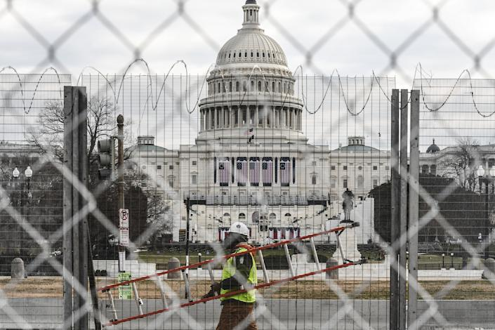 A worker carries a ladder past the Capitol building on the National Mall on January 19, 2021 in Washington, DC. Tight security measures are in place for Inauguration Day due to greater security threats after the attack on the U.S. Capitol on January 6. (Stephanie Keith/Getty Images)