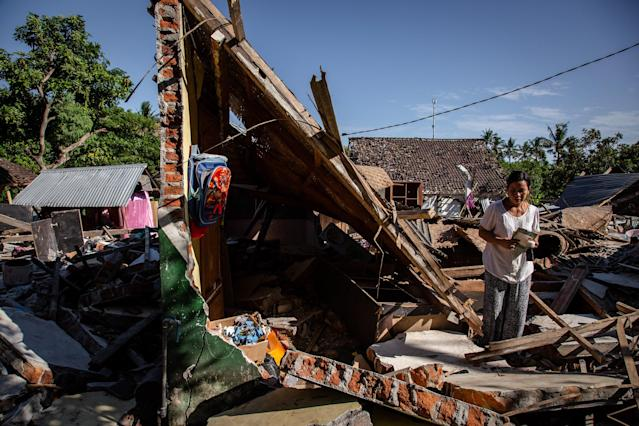 <p>A woman search her belongings at ruins of her houses following an earthquake in Pemenang on Aug. 8, 2018 in Lombok Island, Indonesia. (Photo: Ulet Ifansasti/Getty Images) </p>