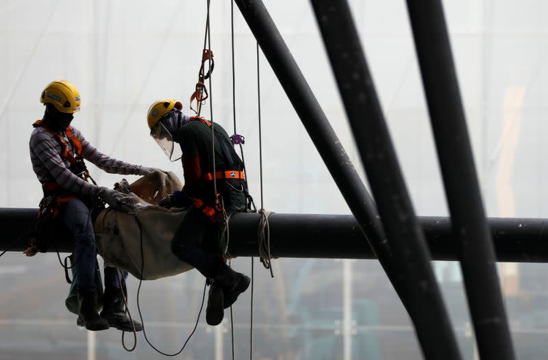 Construction workers are suspended on a steel beam at a work site in Singapore