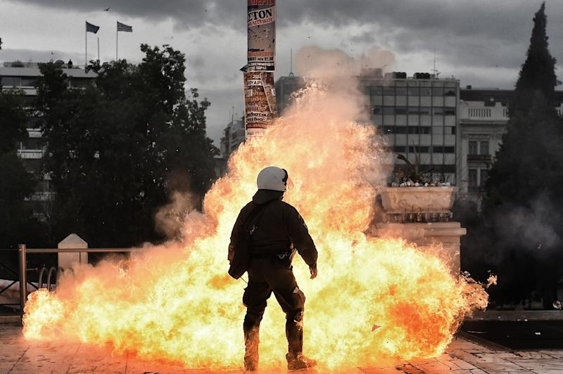 A firebomb explodes beside a riot policeman during a massive protest on February 4, 2016 (AFP Photo/Aris Messinis)