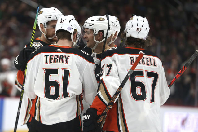 Anaheim Ducks Tory Terry (61) and Rickard Rakell (67) and others surround rookie Brendan Guhle (center) after he scored his first NHL goal against the Arizona Coyotes during the first period of an NHL hockey game Wednesday, Nov. 27, 2019, in Glendale, Ariz. (AP Photo/Darryl Webb)