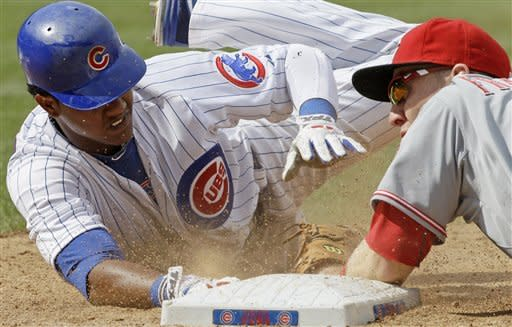 Chicago Cubs' Starlin Castro, left, dives back to first base as Cincinnati Reds first baseman Todd Frazier applies a late tag during the sixth inning of a baseball game in Chicago, Friday, Aug. 10, 2012. (AP Photo/Nam Y. Huh)