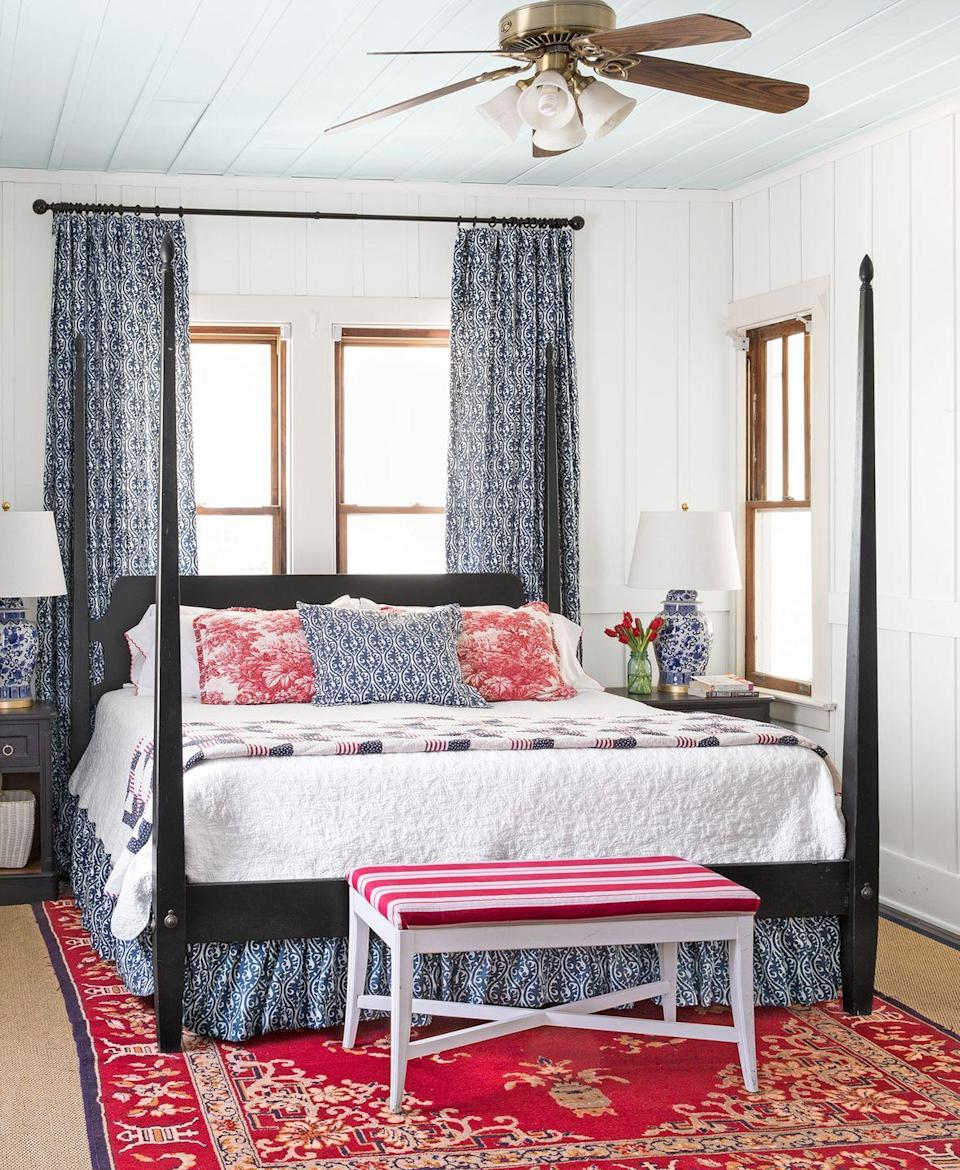 <p>From a bold red area rug to eye-catching window treatments, there's no shortage of romantic details in this bedroom. </p>