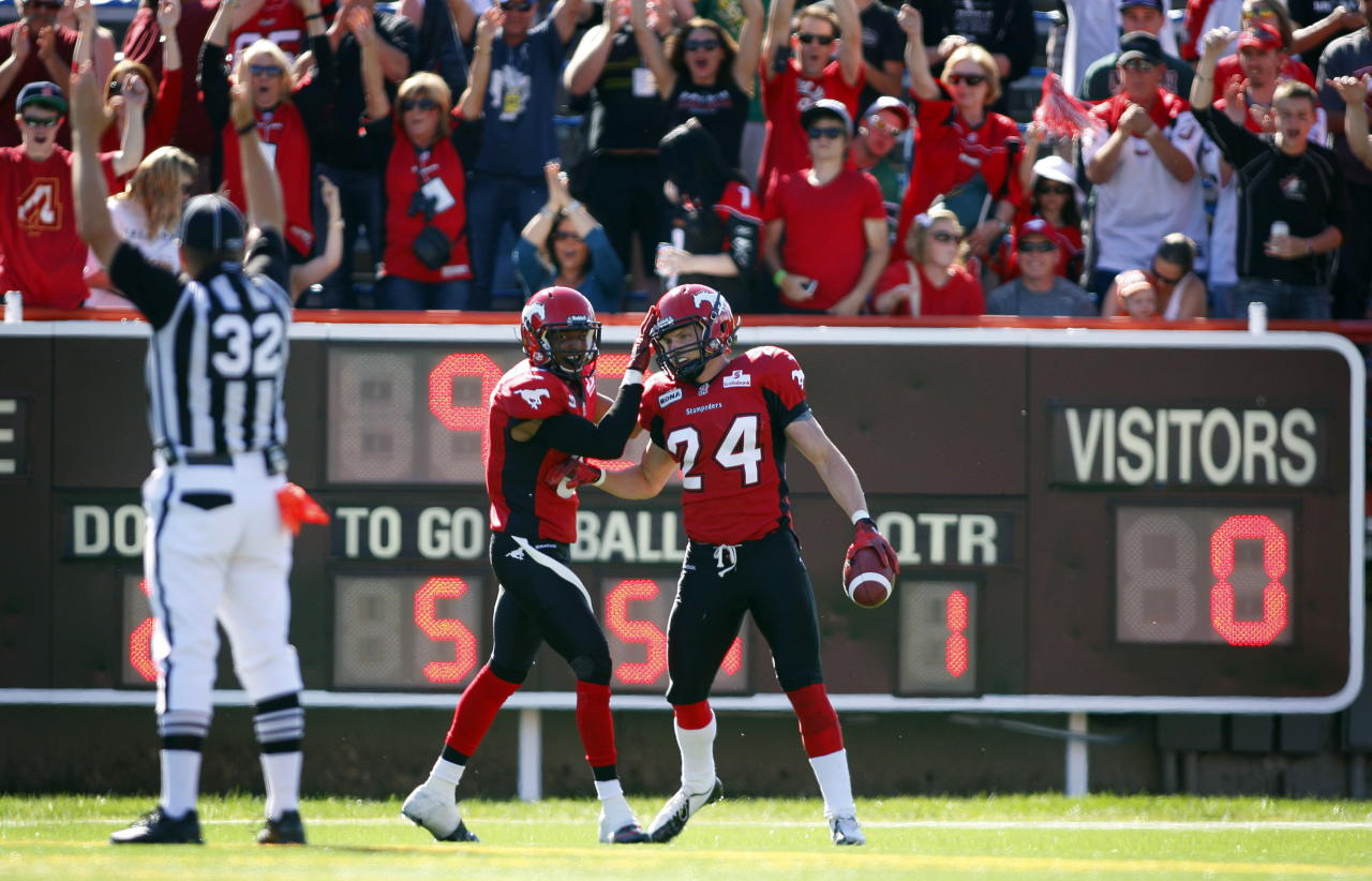 Calgary Stampeders' Keenan MacDougall, right, celebrates his interception touchdown with teammate Quincy Butler during first half CFL football action against the Montreal Alouettes in Calgary, Alta., Sunday, July 1, 2012. THE CANADIAN PRESS/Jeff McIntosh