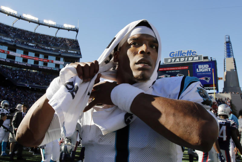 Cam Newton leaves the field with a towel on his head.