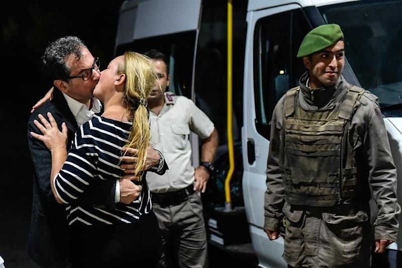 Cumhuriyet editorial director Kadri Gursel kisses his wife after being released from prison in September, but four of his colleagues remained behind bars (AFP Photo/YASIN AKGUL)