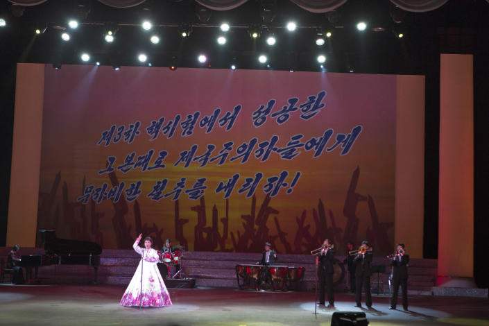 """A North Korean musical performance is held in Pyongyang with  the words """"Let's strike the imperialists mercilessly with the same success we had carrying out the 3rd nuclear test"""" projected on a screen, on Sunday, Feb. 17, 2013. (AP Photo/David Guttenfelder)"""