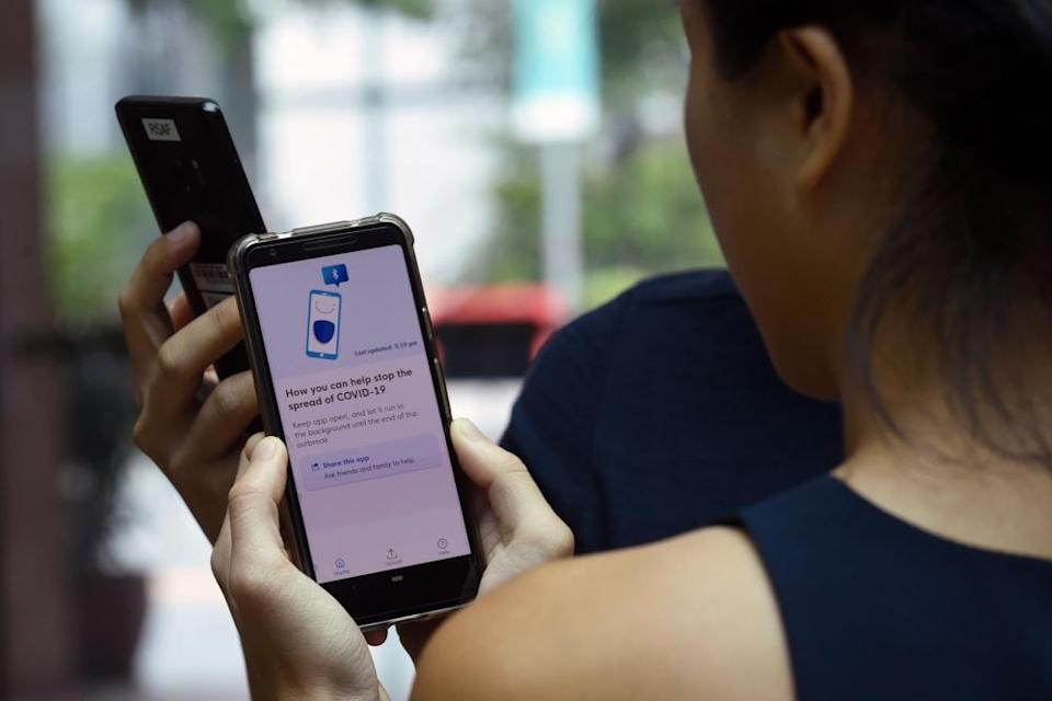 A woman in singapore looks at a smartphone with the contact-tracing app on it.