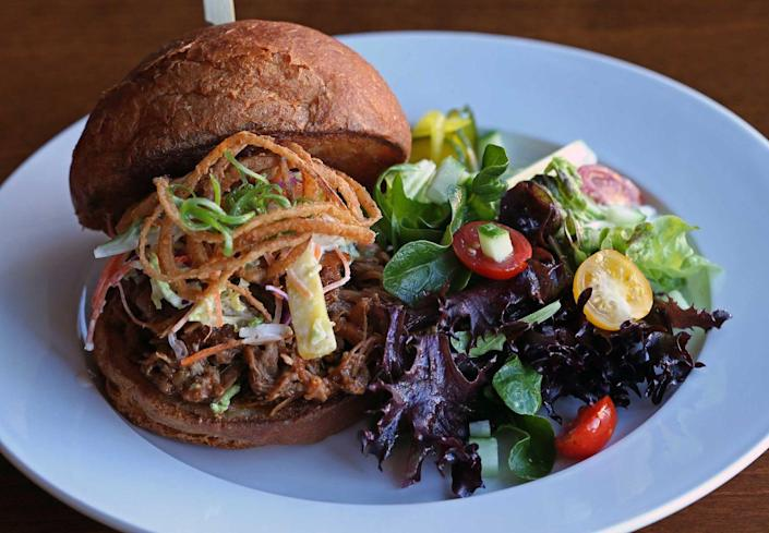 """<p><strong>Kalua Pork Sandwich</strong></p><p>You won't find this anywhere else in the country, and no one does this Hawaiian staple better than <a href=""""https://www.konosnorthshore.com/"""" rel=""""nofollow noopener"""" target=""""_blank"""" data-ylk=""""slk:Kono's"""" class=""""link rapid-noclick-resp"""">Kono's</a>. The pork is slow-roasted for twelve hours and served not only as a variation of sandwiches but also in a breakfast burrito, biscuit or nachos. Sandwiches include guava barbecue sauce, grilled onions, ham and bacon.</p>"""