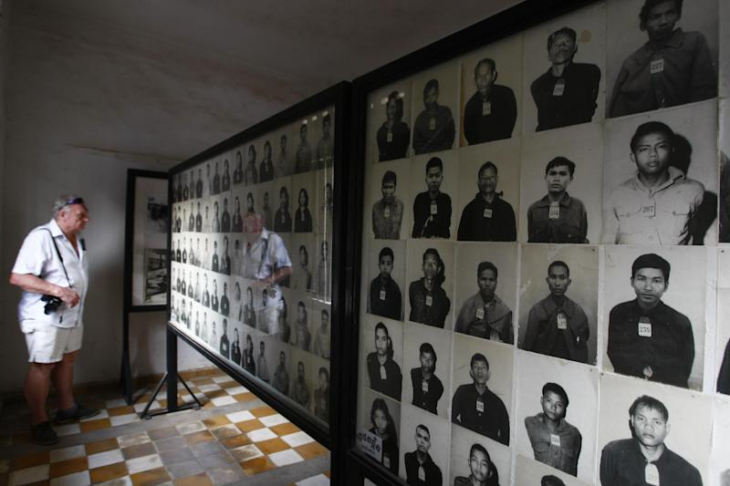 "In this photo taken Thursday, Feb. 20, 2014, a tourist looks at portraits of genocide victims at the Tuol Sleng Genocide Museum, formerly the most notorious Khmer Rouge prison, in Phnom Penh, Cambodia. The office of Cambodia's most celebrated filmmaker is filled with books on the Khmer Rouge - on his desk, on the walls, in the filing cabinets and in every corner of Rithy Panh's dimly lit office are memories of his country's national tragedy. In his latest movie, the 51-year-old filmmaker focuses for the first time on his personal story of loss and tormented survival. ""The Missing Picture"" won an award at last year's Cannes Film Festival and is up for Best Foreign Language Film at the Oscars this weekend, marking the first time a Cambodian film has been nominated for an Academy Award. (AP Photo/Heng Sinith)"