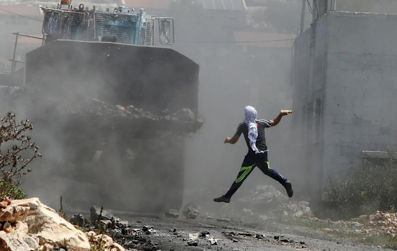 A Palestinian protester throws a bottle filled with paint at an Israeli army bulldozer following a demonstration against the expropriation of Palestinian land by Israel in the village of Kfar Qaddum, in the occupied West Bank, on August 21, 2015