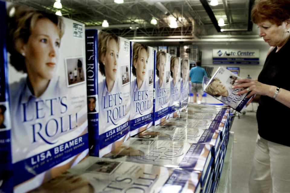 """FILE - In this Tuesday, Aug. 20, 2002 file photo, a woman looks a copy of """"Let's Roll!"""" by Lisa Beamer at Sam's Club in West Windsor, N.J., after it went on sale. Beamer's husband, Todd, died when hijacked United Airlines Flight 93 plunged into the Pennsylvania countryside on Sept. 11. Before the crash, a cell phone operator heard Todd Beamer say """"let's roll"""" as he and other passengers attempted to overpower the hijackers. (AP Photo/Daniel Hulshizer, File)"""
