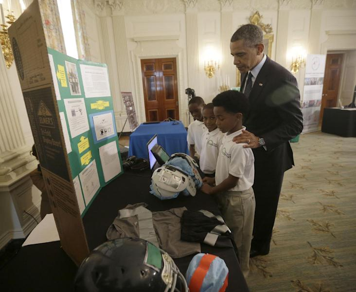 President Barack Obama, listens to, from left, Evan Jackson, 10, Alec Jackson, 8, and Caleb Robinson, 8, all from McDonough, Georgia, as they explain their 'COOL PADS', a cooling system in football shoulder pads that keep players safe from overheating, Monday, April 22, 2013, at the White House Science Fair event in the State Dinning Room of the White House in Washington. (AP Photo/Pablo Martinez Monsivais)