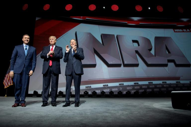 US President Donald Trump stands with National Rifle Association (NRA) President Wayne LaPierre (R) and NRA-ILA Executive Director Chris Cox (L) during the NRA Leadership Forum in Atlanta, Georgia on April 28, 2017