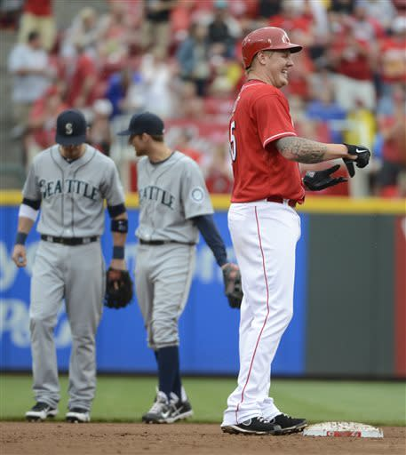 Cincinnati Reds' Mat Latos, right, celebrates after hitting a two-run double in the fourth inning of a baseball game against the Seattle Mariners at Great American Ball Park in Cincinnati, Saturday, July 6, 2013. (AP Photo/Michael E. Keating)