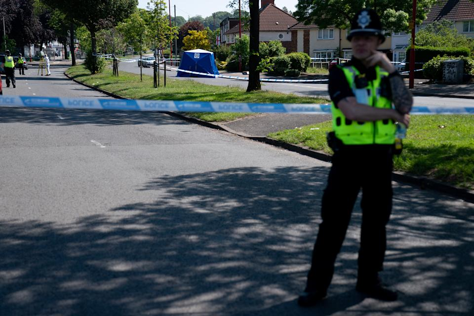 A police officer stands near the scene on College Road, Kingstanding, north of Birmingham, where a 14-year-old boy died after being stabbed on Monday evening. Police have launched a murder investigation and are hunting up to seven people in connection with the attack. Picture date: Tuesday June 1, 2021.