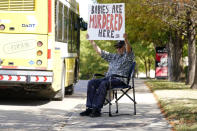 David Trujillo holds a sign a bus drives by on the street in front of a building housing an abortion provider in Dallas, Thursday, Oct. 7, 2021. A federal judge has ordered Texas to suspend a new law that has banned most abortions in the state since September. The order Wednesday by U.S. District Judge Robert Pitman freezes for now the strict abortion law known as Senate Bill 8. (AP Photo/LM Otero)