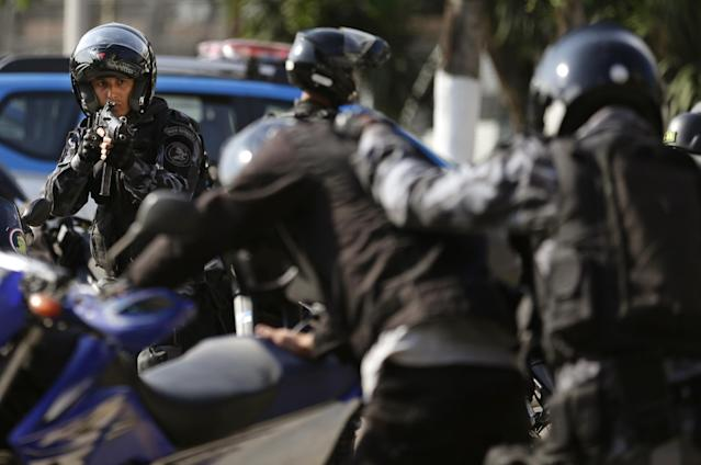 A police officer in riot gear aims his weapon at a person playing the part of a protester during a security drill in preparation for the World Cup in Rio de Janeiro, Brazil, Thursday, May 15, 2014. The FBI is helping to train Brazil's civilian police, military officers, municipal guards and firefighters on how to manage demonstrations ahead of the international soccer tournament that starts in June. (AP Photo/Hassan Ammar)