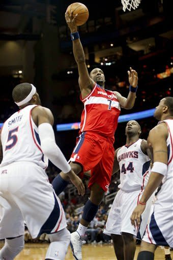 Washington Wizards' Andray Blatche drives to the basket against Atlanta Hawks' Josh Smith (5) and Ivan Johnson (44) during the first half of an NBA basketball game in Atlanta, Friday, March 16, 2012. (AP Photo/Rich Addicks)