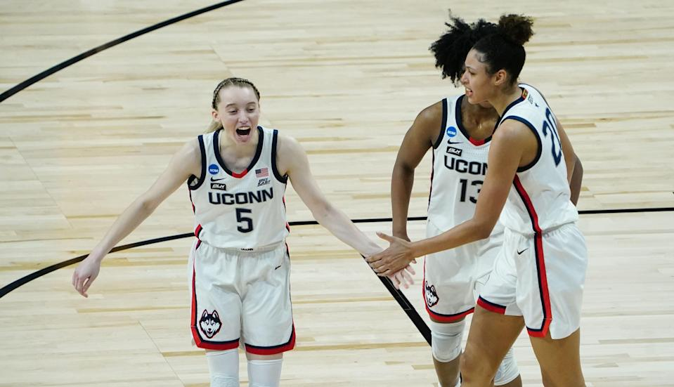 Connecticut's players Paige Bueckers (5) , Christyn Williams (13) and Olivia Nelson-Ododa (20) celebrate after beating Iowa in the Sweet 16.