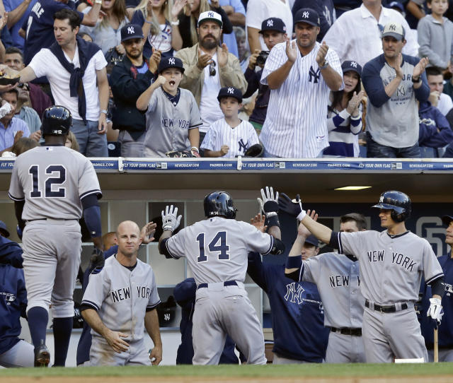 New York Yankees' Curtis Granderson is greeted at the dugout after his two-run home run against the San Diego Padres in the seventh inning of an interleague baseball game in San Diego, Saturday, Aug. 3, 2013. (AP Photo/Lenny Ignelzi)