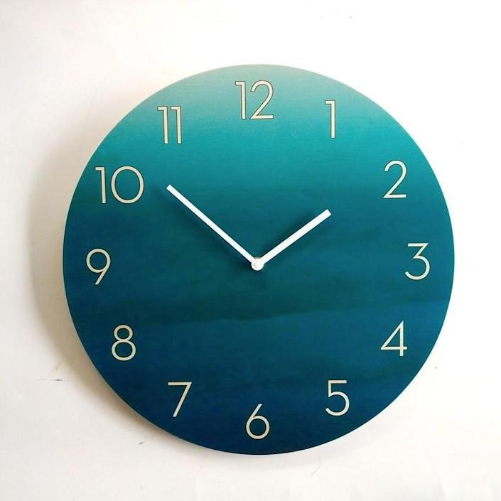 """This ombre teal is reminiscent of the ocean. Prefer a different color? The Etsy artisan notes that the color scheme or fonts can be customized for no additional charge. The clock is available in three sizes: 7.9, 11.2, or 15 inches. $35, Etsy. <a href=""""https://www.etsy.com/listing/948104376/objectify-ombre-teal-wall-clock-with"""" rel=""""nofollow noopener"""" target=""""_blank"""" data-ylk=""""slk:Get it now!"""" class=""""link rapid-noclick-resp"""">Get it now!</a>"""