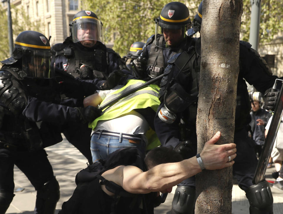 A police officer scuffle with protestors during a yellow vest demonstration in Paris, Saturday, April 20, 2019. French yellow vest protesters are marching anew to remind the government that rebuilding the fire-ravaged Notre Dame Cathedral isn't the only problem the nation needs to solve. (AP Photo/Francisco Seco)