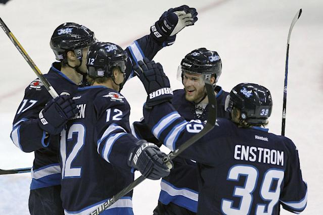 Winnipeg Jets' James Wright (17), Olli Jokinen (12), Matt Halishchuk (15) and Toby Enstrom (39) celebrate Jokinen's goal against the St. Louis Blues during the first period of an NHL hockey game, Friday, Oct. 18, 2013 in Winnipeg, Manitoba. (AP Photo/The Canadian Press, John Woods)