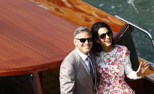 George and Amal Clooney wave from a taxi boat in Venice, Italy, on the morning after their September 2014 wedding. (Photo: Pierre Teyssot/AFP/Getty Images)
