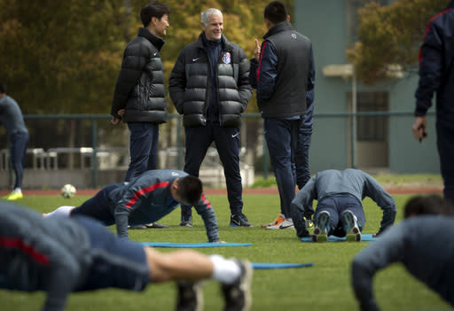 In this Thursday, April 9, 2015 photo, French manager Francis Gillot, center, talks with assistants as his Shanghai Shenhua soccer squad warms up during practice at the team's training facility in Shanghai. While a few years ago Chinese Super League (CSL) soccer was mired in corruption scandals and poor play, Shenhua is emblematic of the new and improved CSL - it's increasingly globalized, brimming with newfound professionalism and flush with cash. (AP Photo/Mark Schiefelbein)