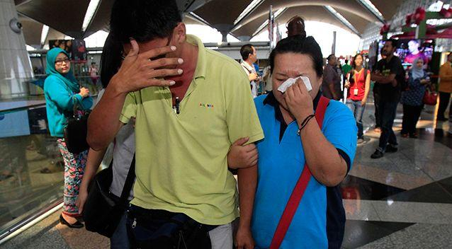 A woman wipes her tears after walking out of the reception center and holding area for family and friend of passengers aboard a missing Malaysia Airlines plane. Photo: AP