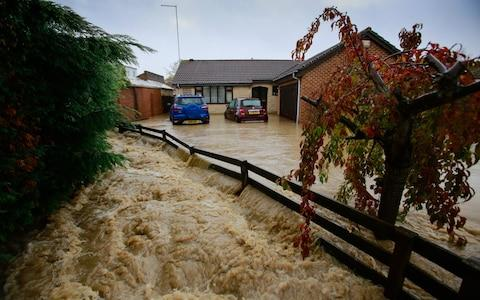Homes are severely flooded as raging flood water rises in the village of Whiston near Sheffield - Credit: SWNS
